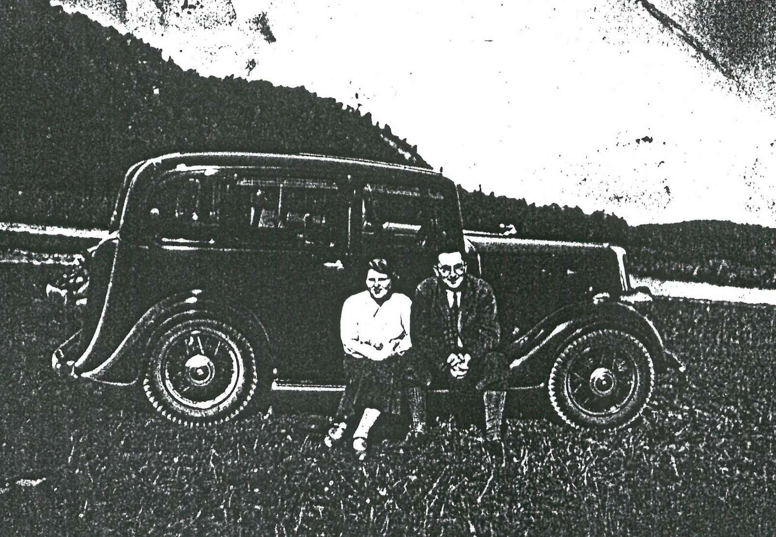 Black-and-white-photo: Two persons with car.