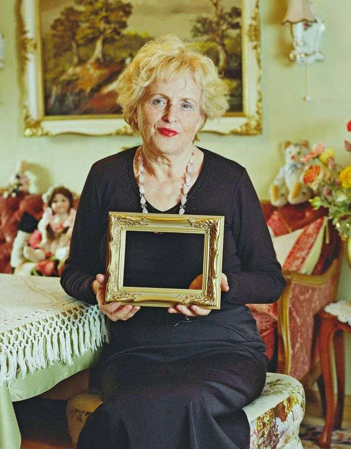 Colour photo: Older woman with an empty frame in her hands.