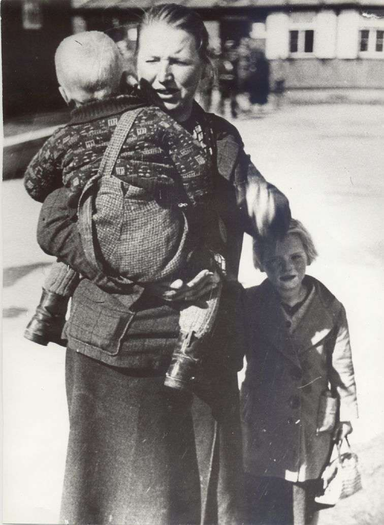 Black-and-white-photograph: Woman with a little girl and a baby in her arm.