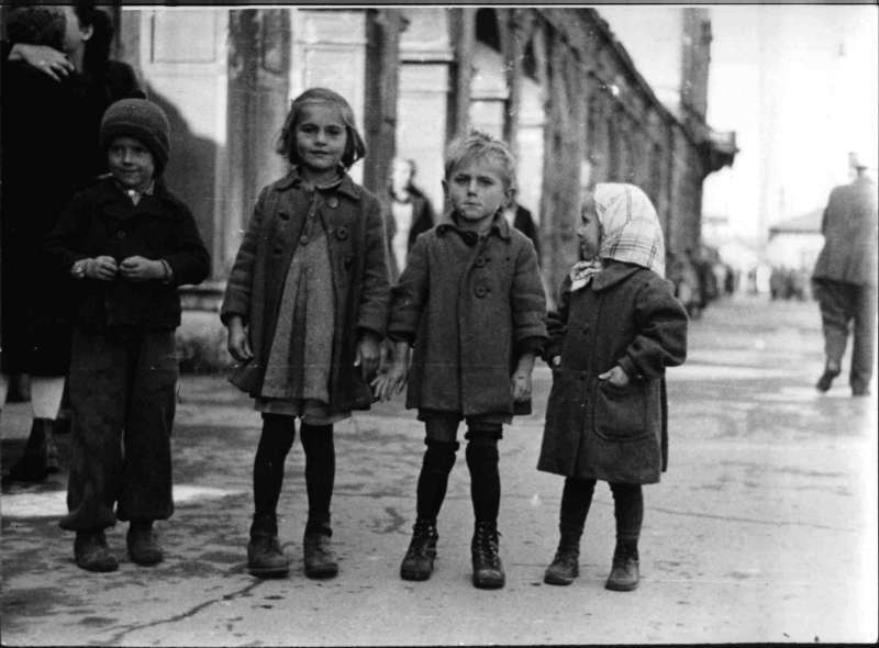 Black-and-white-photograph: Four children on the street.