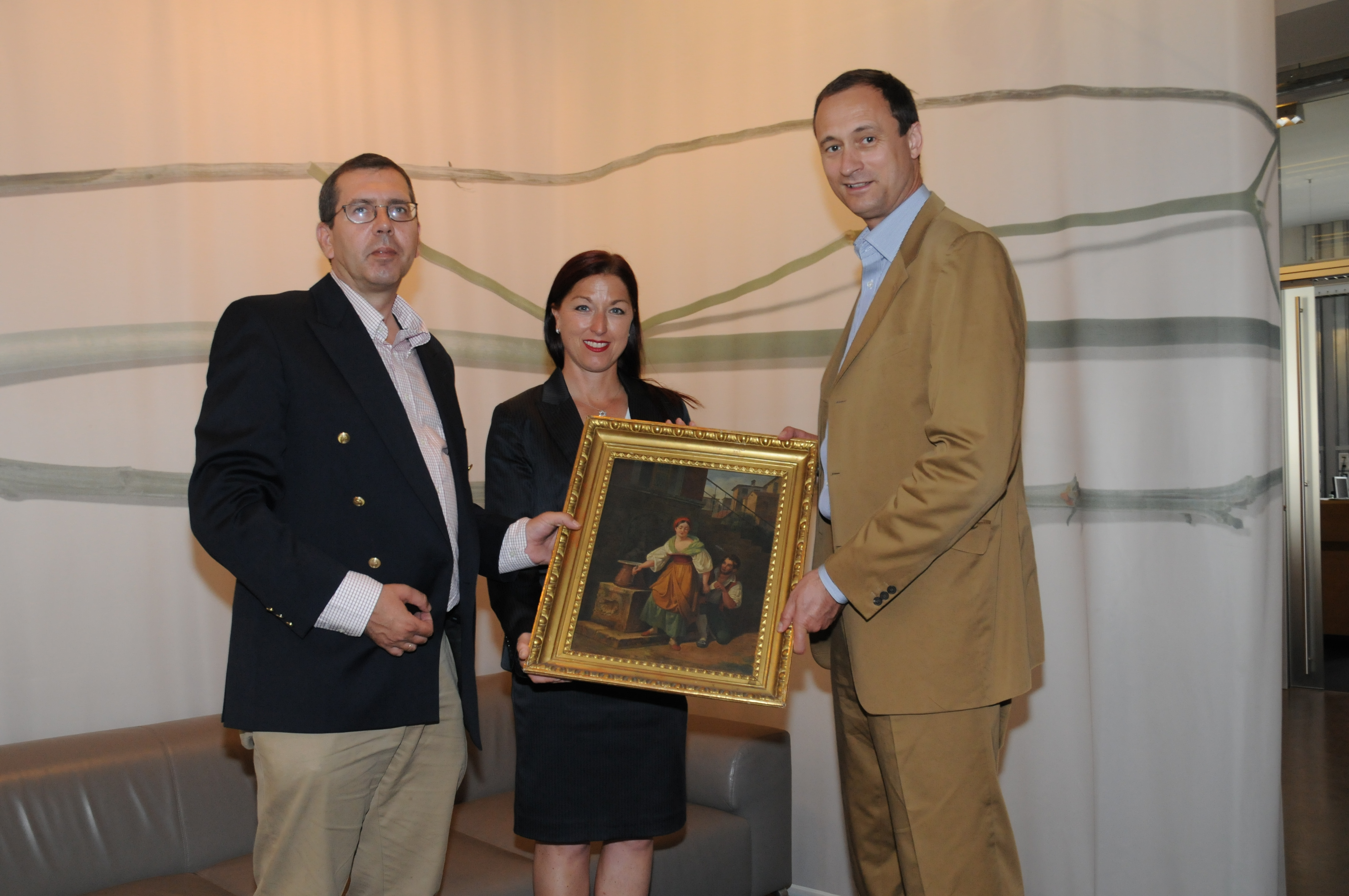 Provenance researcher Dr. Michael Wladika (left) and Municipal Councilor Dr. Andreas Mailath-Pokorny (right) present the restituted painting 'The Love Letter' by Johann Nepomuck Schödlberger to Secretary General Hannah Lessing.